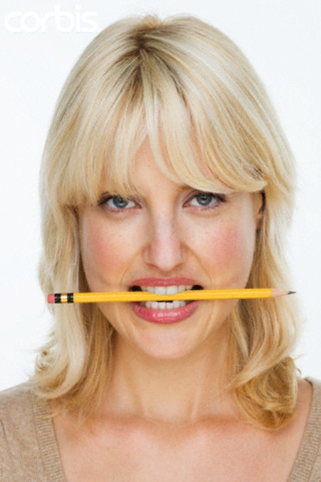 Woman Biting Pencil --- Image by © Tom Grill/Corbis