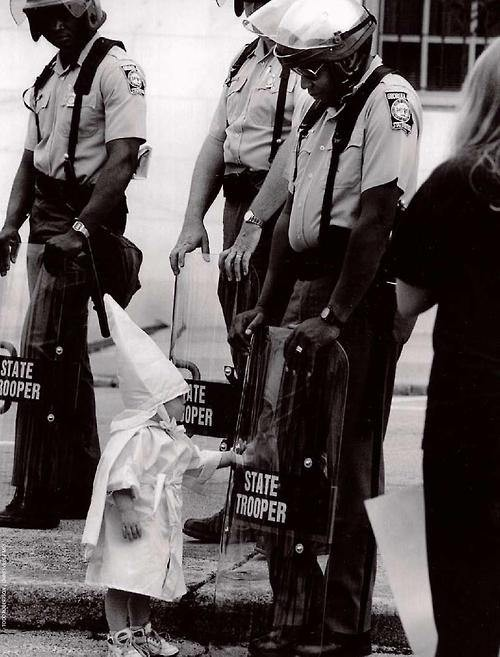 The%20child%20of%20a%20KKK%20member%20touches%20his%20reflection%20in%20an%20African%20American%20police%20officer%27s%20riot%20shield%20during%20a%20demonstration.%20%5B1992%5D