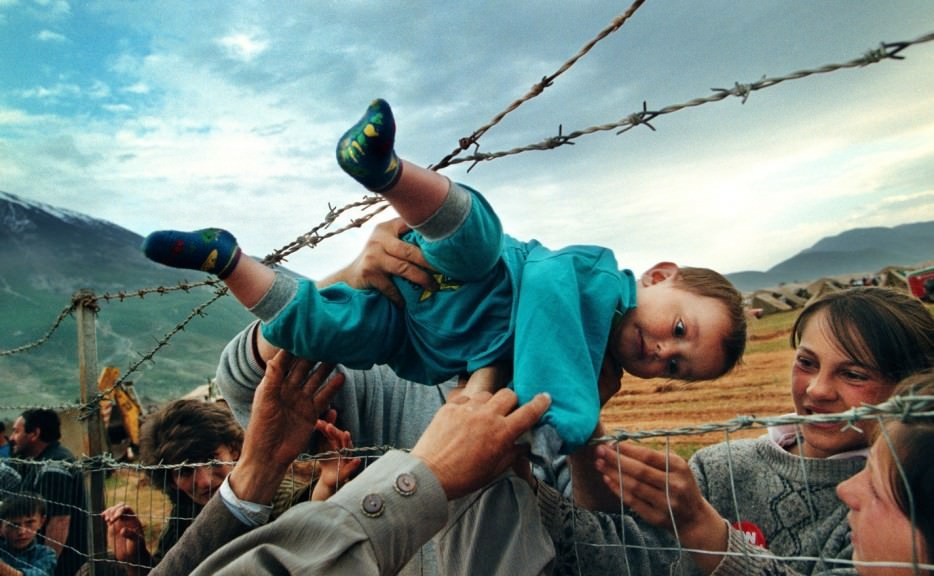 Agim%20Shala%20is%20passed%20through%20a%20barbed%20wire%20fence%20to%20his%20grandparents%20at%20a%20camp%20for%20refugees%20of%20the%20Kosovo%20War
