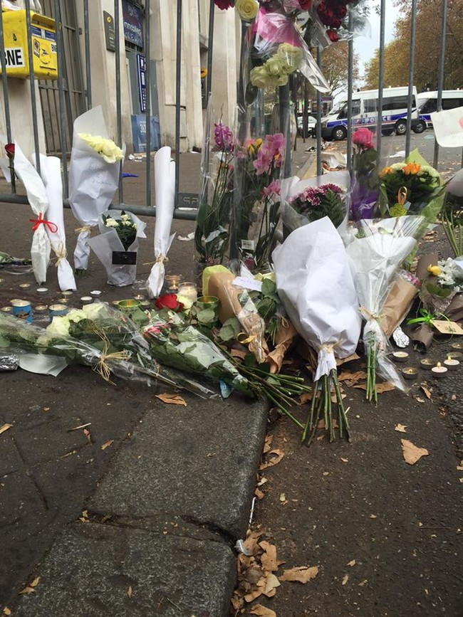 """""""[At] the Bataclan [...] flowers and candles were mixed in with latex gloves and medical supplies. A pair of shoes was left in the middle of the street. There were tons of reporters but you thankfully cannot get close to the theater, where work is clearly ongoing. I'm not sure how you do that work."""""""